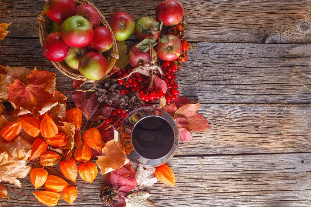 Fall wine with harvest on rustic wooden background